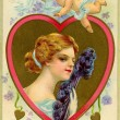 A vintage Valentine card with cupid flying over a woman with a f — Stock Photo