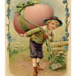 Stockfoto: Vintage Easter postcard of boy with large Easter egg on hi