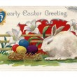 A vintage Easter postcard of lilies  a white rabbit and Easter eggs — Stockfoto