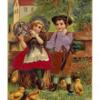 Stockfoto: Vintage Easter postcard of little boy and girl surrounded by