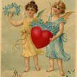 A vintage Valentine postcard with two angels holding a heart and — Stock Photo #12429803