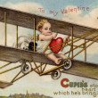 A vintage Valentine card with cupid flying an airplane with a st — Stock Photo