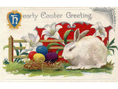 A vintage Easter postcard of lilies a white rabbit and Easter eggs — Stock Photo