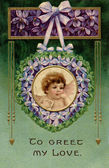 A vintage Valentines postcard with a cherub holding a love lette — Stock Photo