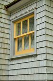Yellow trimmed window on cedar shake house — Stock Photo