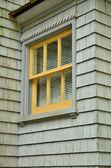 Yellow trimmed window on cedar shake house — Stock Photo