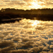 Mirrored cloud filled sunrise - Stock Photo