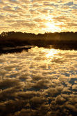 Mirrored cloud filled sunrise — Stock Photo