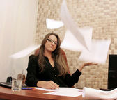 Business woman with papers flying up — Stock Photo
