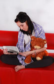 Pretty woman sitting on the couch reading the book to teddy bear — Stock Photo