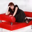 Woman laying on red sofa — Stock Photo
