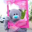 Holiday teddy bear with a pink frame — Stock Photo
