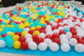 Balloons, red, blue, yellow and white floating in a pool — Stock Photo