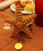 Decorative orange sea star on table with glass — Stock Photo
