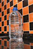 Plastic bottle of water and glas — Stock Photo