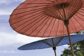 Red and blue beach umbrella with blue sky. — Stock Photo