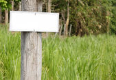 White blank signboard  in the meadow. — Stock Photo