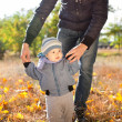 Baby boy taking first steps with father help — Stock Photo