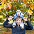 Young father with his son outdoor in the autumn park — Stock Photo