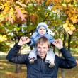 Stock Photo: Young father with his son outdoor in the autumn park
