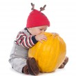 Cute baby boy in funny deer hat with orange pumpkin on white — Stock Photo #13338640