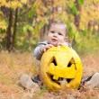 Baby boy outdoors with real pumpkin — Stock Photo