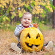 Baby boy outdoors with real pumpkin — Stock Photo #13338658