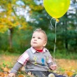 Baby boy sitting in autumn leaves holding a smiley faced balloon — Stock Photo