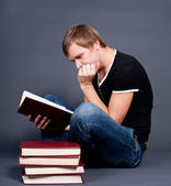 Pensive young man studying on a stack of books — Stock Photo