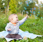 Boy sitting on green grass outdor playing with soap bubbles — Stock Photo