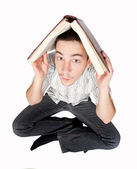 Student holding a book over his head — Stock Photo