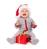 Baby in Santa hat playing with Christmas gift box isolated — Stock Photo