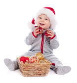 Baby in Santa hat playing with Christmas balls isolated on white — Stock Photo