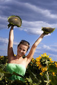 Young beautiful woman between sunflowers — Stock Photo