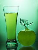 Apple juice and Apple on a green background — Photo