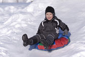 Happy boy slide down the hill. Cold winter. — Zdjęcie stockowe