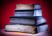 Old books, red light background — Stock fotografie