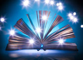 Open old book, mystical blue light at background — Stock Photo