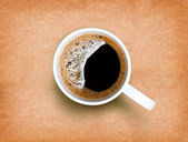 Fresh black coffee in a white cup on paper texture — Stock Photo
