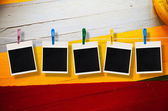 Blank picture frame hanging on clothesline on wood background — Stock Photo