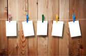 Blank picture frame hanging on clothesline on wood background — Stockfoto