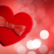 Red heart with red bow, defocused lights on background — Stock Photo