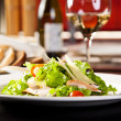 Chicken salad with vegetables and croutons, bottle of wine on th — Stock Photo