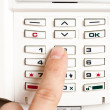 Closeup of a person entering a pin code to a home alarm — Stock Photo