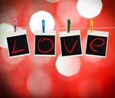 Мгновенные фотографии с словом любовь висит на бельевой веревке, красный Дэфо — Стоковое фото