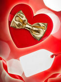 Red heart with golden bow and blank tag, defocused lights on bac — Stock Photo
