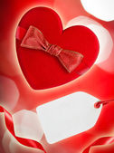 Red heart with red bow and blank tag, defocused lights on backgr — Stock Photo