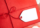 Red gift box with blank gift tag — Stock Photo