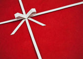 Hand made ribbon and bow on red kraft paper as background. Greet — Stock Photo