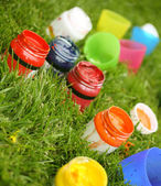 Bright paint colors in the tubes in green grass — Stock Photo